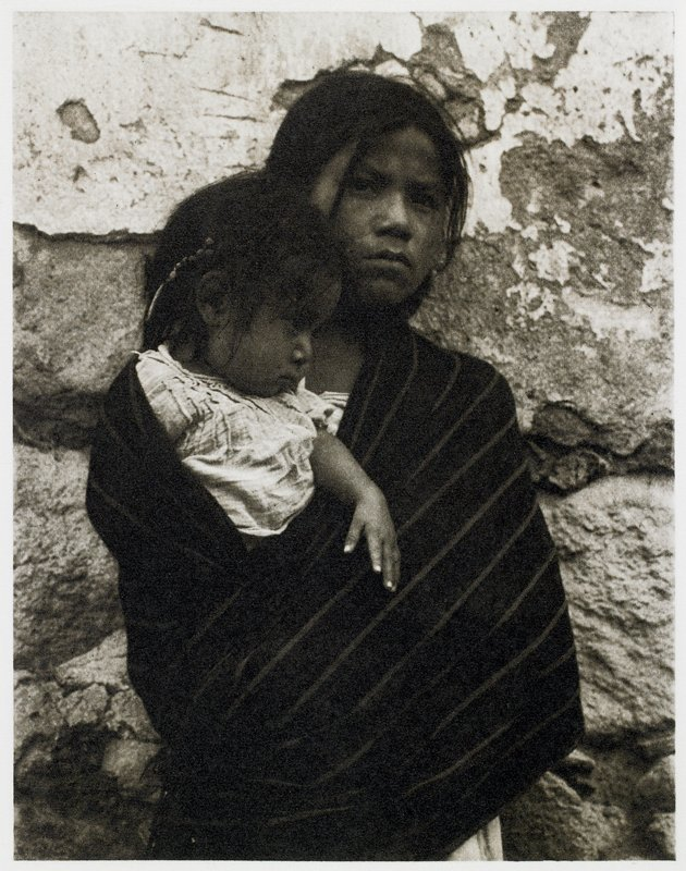 girl wrapped in dark shawl holding small child