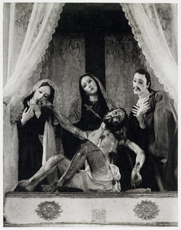 four carved wooden figures framed by lace curtains - the crucified Christ in the center and three figures behind (two women and one man)