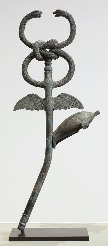 scepter with 2 snakes with knotted bodies at top, a pair of wings below and a bulbous form on a bent stem