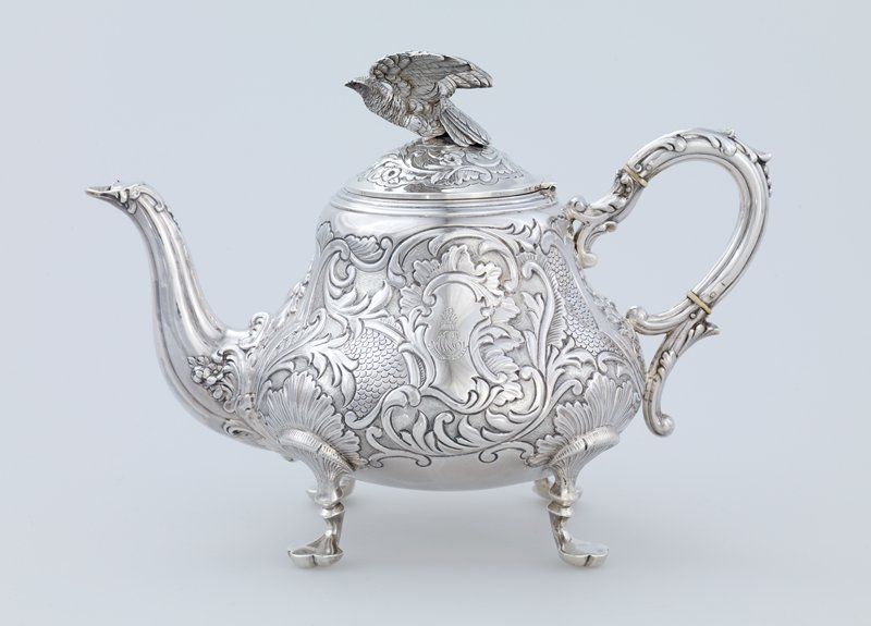 teapot, silver; floral repousee chased pear design body with scroll legs, spread falcon finial