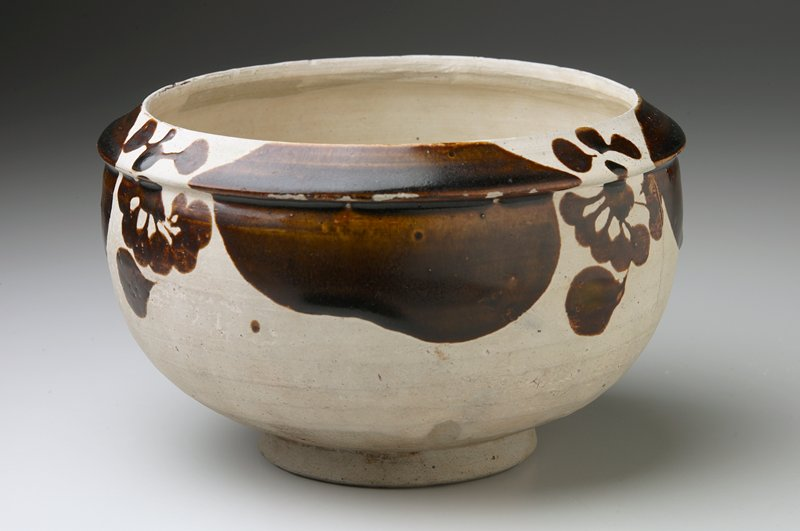 rounded body on raised foot; slightly inward-curving lip; surface decorated with abstracted floral shapes in brown glaze 5 on interior, 4 at lip and outer edge, separated by brown ovals