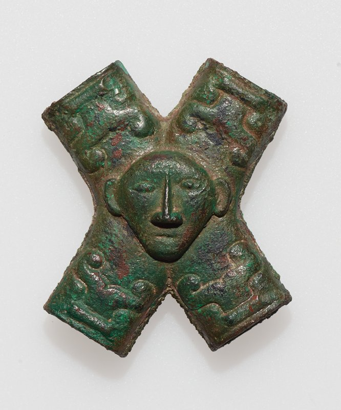 hollow cross-shaped element with human head mask at center, with long nose, small eyes and protruding ears; 4 curvilinear designs at each open end on front; black wire mount