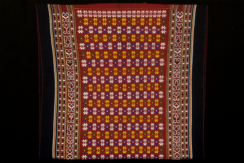central red area with repeated floral design, bordered by 2 vertical bands on each side; 2 selvages; patterning formed by discontinuous supplementary weft