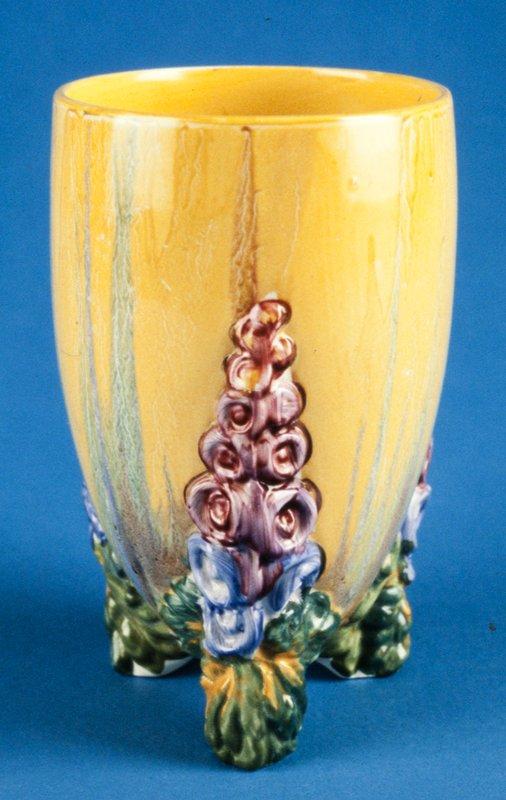 vase ('My Garden' design), three-legged vase with multicolored holly-hocks climbing up legs, yellow underglaze, porcelain