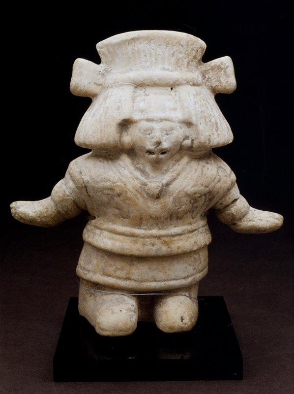 standing female figure, mold made, large headdress, cream colored earthenware with black pigment stand in E1.9