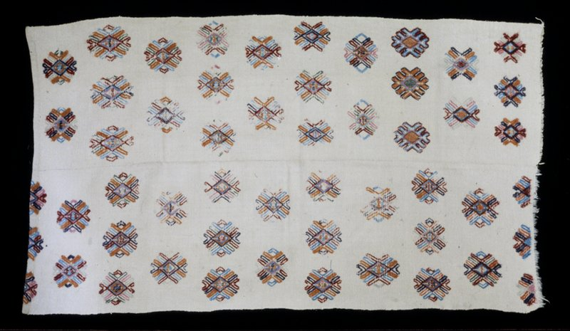 Yattha Dhenkhep, double panel wool brocade on wool background; discontinuous supplementary weft medallion motifs in blues, pinks, orange wool in neutral ground; center seam; one end hemmed, one unfinished