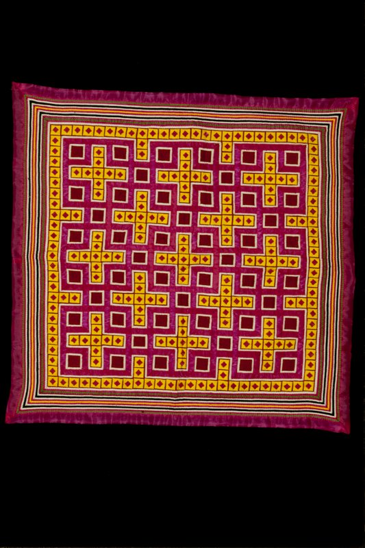 Funeral pillow, polyester, layered border, fold and tuck applique in pink, black, green and yellow. Yellow squares represent vegetable blossoms. Daughters and daughters-in-law make funeral pillows for their parents. Pillows to be placed under the head when parent is buried.