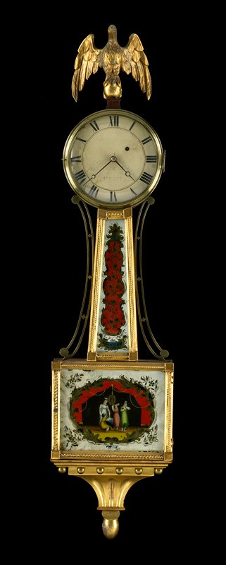 glass with reverse painting, rope moulding, 8 day brass weight powered movement, pendulum regulated, brass bezel surrounding dial, brass side pieces, eagle finial