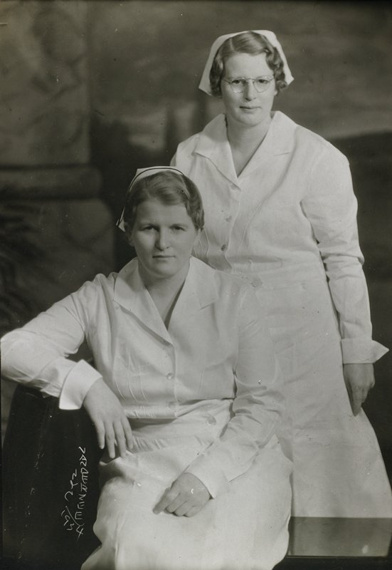 two nurses dressed in white uniforms with white caps; one seated, one standing