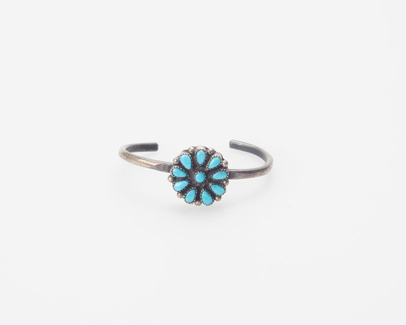 Child's Bracelet; wire set with Zuni cluster of one round and nine pear-shaped turquoises in serrated bezels with silver drops between. J.#377, Cat.#345.