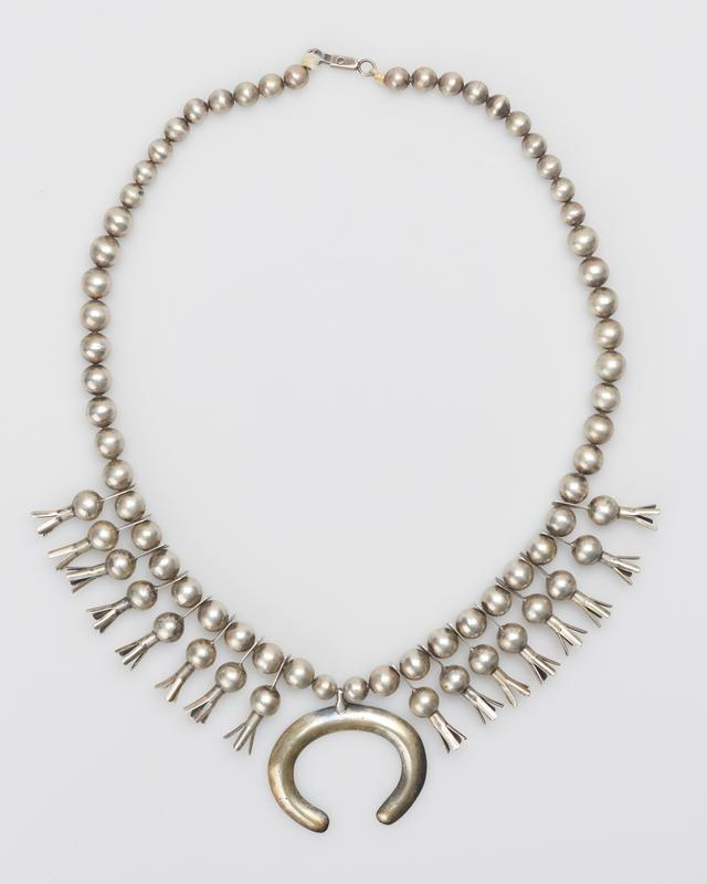 Single strand of large plain silver beads; 8 4-pronged squash blossoms on each side with pierced extensions; 'Roanhorse' cast naja; on string with silver clasp. J.#419, Cat.#393.