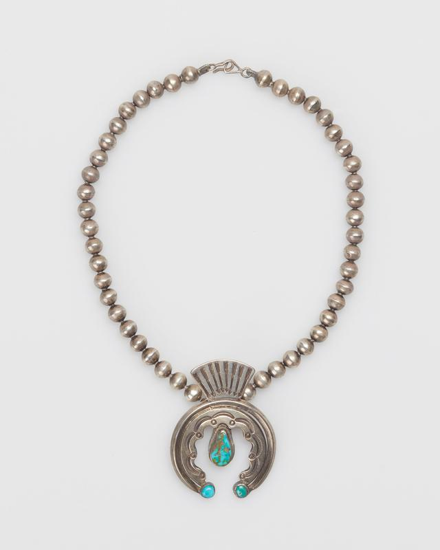 Single strand of medium silver beads; cast silver naja of carinated wire enclosing scalloped sheet crescent, set with one pear shaped Blue Gem turquoise on center tap with two round Blue Gem Turquoises at terminals; sheet ornament with stamped decoration above shank(stamped arrow design) silver clasp and chain. J.#430, Cat.#405.
