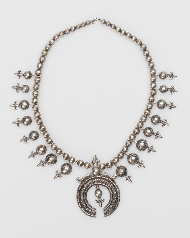 """Cast single strand with medium silver beads;sixteen graduated hemispheres terminating in cast """"cornflowers""""; carinated and square wire naja with """"cornflower"""" bead pendant; stamped decoration; silver clasp and chain. J.#429, Cat.#470."""