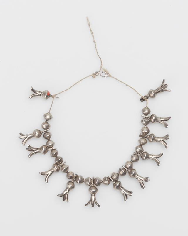 Silver beads and 11 4-pronged squash blossoms with filed design. J.#500, Cat.#368.