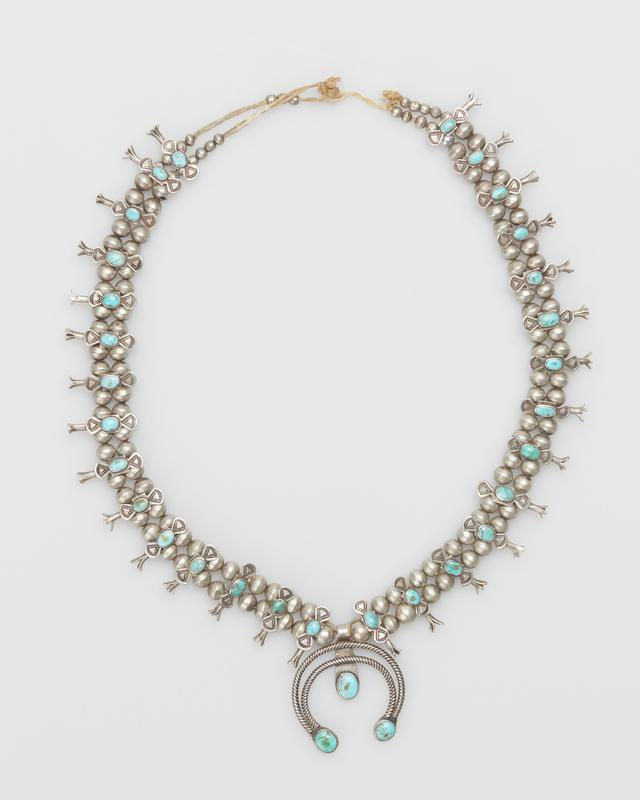 """Double strand of silver beads; twenty nine small squash blossoms overlaid with """"butterfly"""" plaques set with small elliptical turquoises; double naja of twisted square wire, set with three round turquoises; string and knot. J.#448, Cat.#424."""