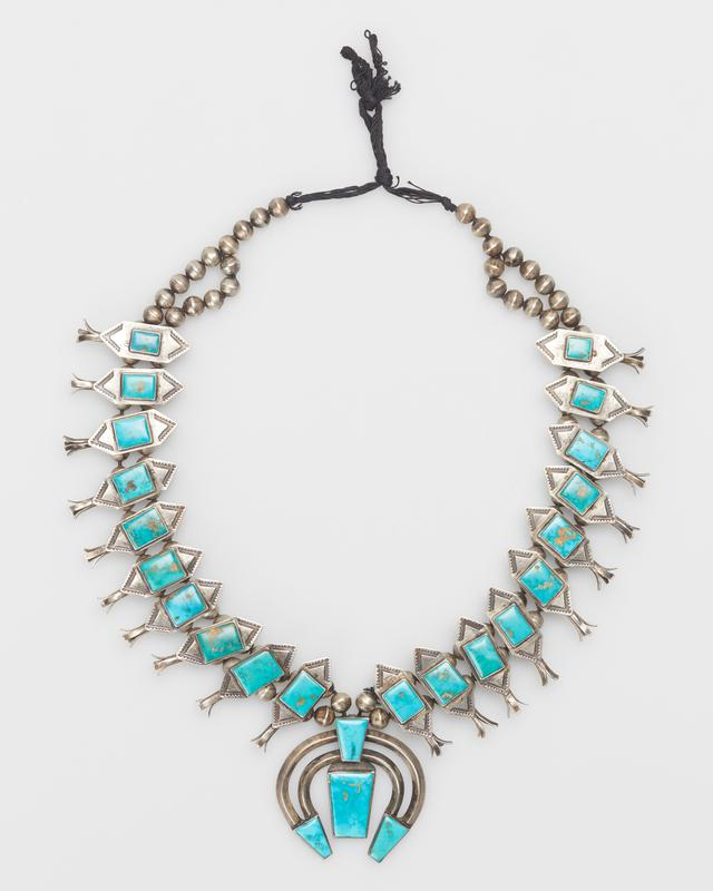 Double strand of silver beads with 20 butterfly sq. bloss.with square Blue Gem turquoises; , and double band cast naja set with four trapezoidal Blue Gem turquoises, turquoise at pts. and on top, 24 stones in all. J.#458, Cat.#426.