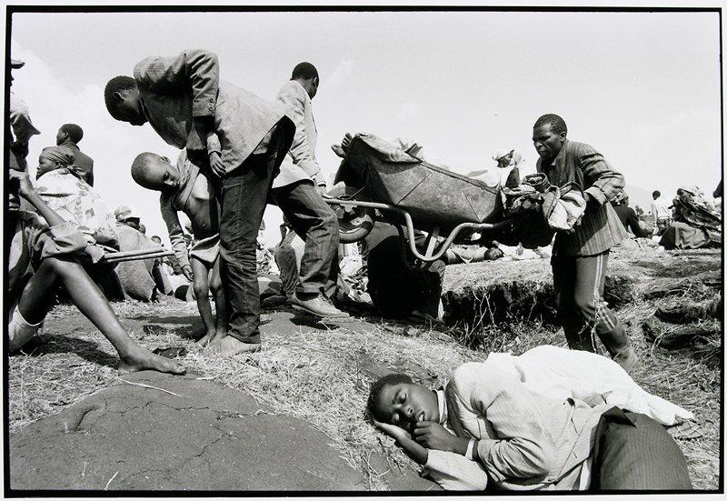 man laying down, men behind carrying wheelbarrow