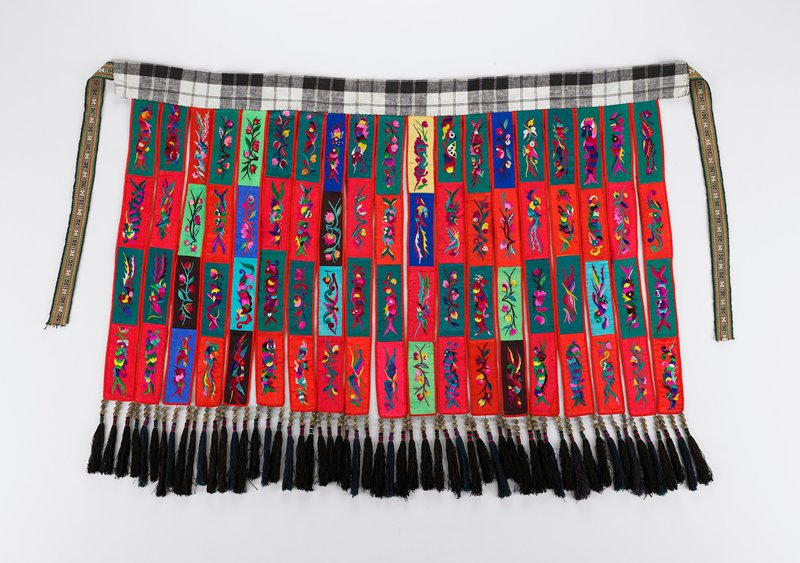 black and white checked waist band with nineteen cloth bands hanging from it; each band is divided into four distinct plant or animal designs embroidered; field colors include light and dark blue, green, red and yellow; three groups of fringe are attached to each band; blue backing on bands
