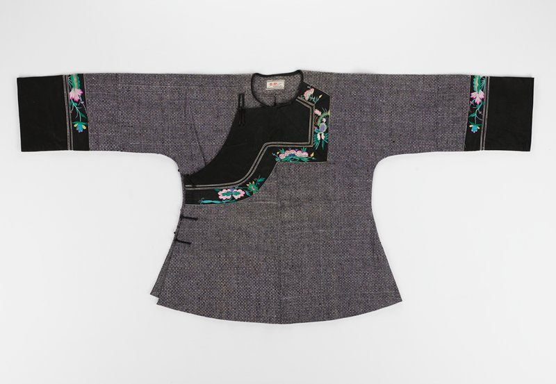 basket weave design in black and white throughout body, solid black bands for arm cuffs and an additional thin arm band of embroidered floral design, button down right side; front black panel at neck with embroidered band from neck to right side