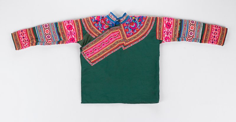 green shirt that buttons on one side under sleeve; upper portion of shirt is embroidered on front and back; sleeves are completely covered with embroidery