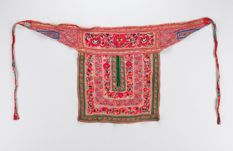 red waistband decorated with one horizontal band of embroidery showing fuchsia flowers and birds; green fabric of main body decorated with three large embroidered bands forming a squared 'U' shape; two bands on main body show birds and flowers