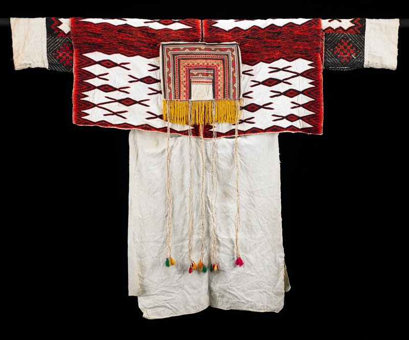 plain white skirt beneath shoulder flaps of white fabric with red and dark blue embroidery with heavy yarn; long sleeves under shoulder flaps also embroidered in heavy yarn (blue, brown and red); center of chest decorated with ribbons forming top half of a rectangle, short gold tassels and long multicolored tassels