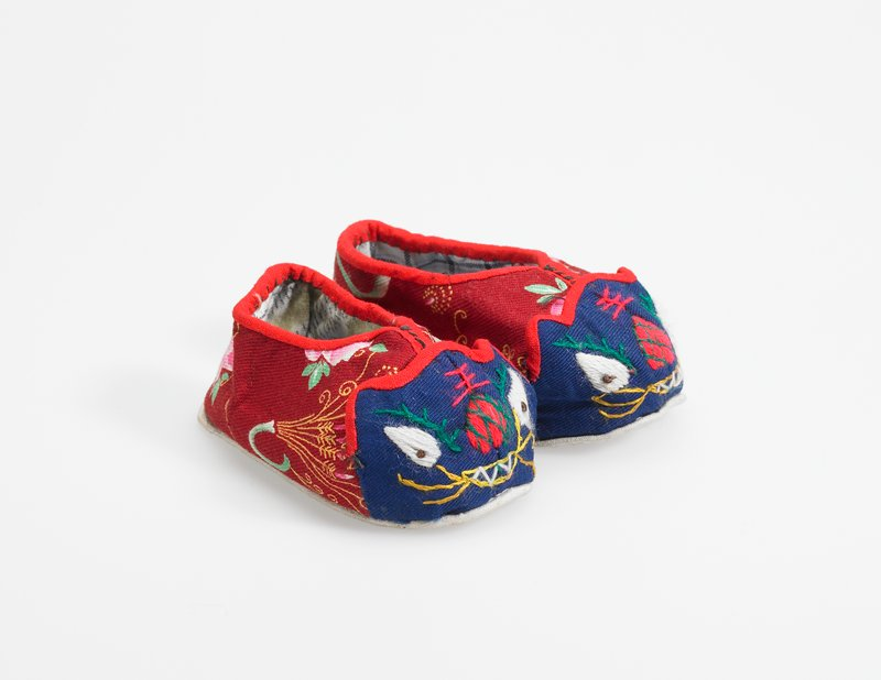 maroon baby shoes with red trim; cat face is depicted on blue background on toe area of each shoe