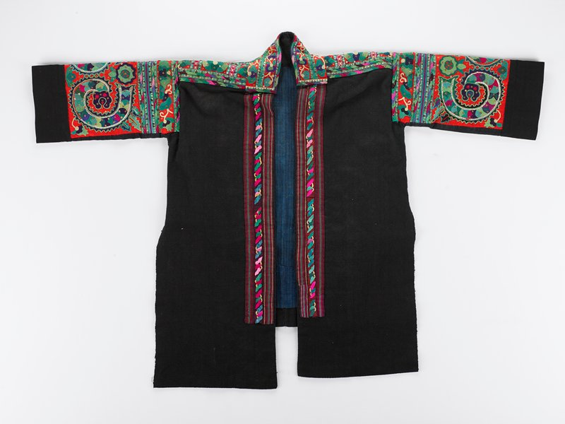 black field with collar, shoulder and upper arm embroidery in green, red, blues and black in an organic design, plain back, bands of decoration on both sides of front opening