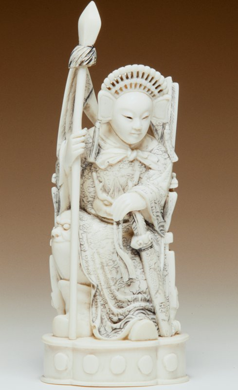 carved ivory seated figure in warrior dress, holding a spear in proper right hand