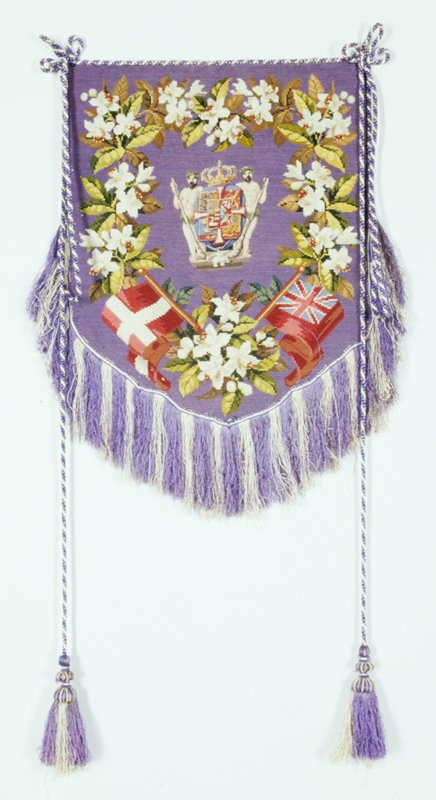 purple ground with two men in center next to shield; floral border; two flags at bottom, purple and white fringe on bottom half; 2 purplr and white tasseled cords; British commonwealth nation