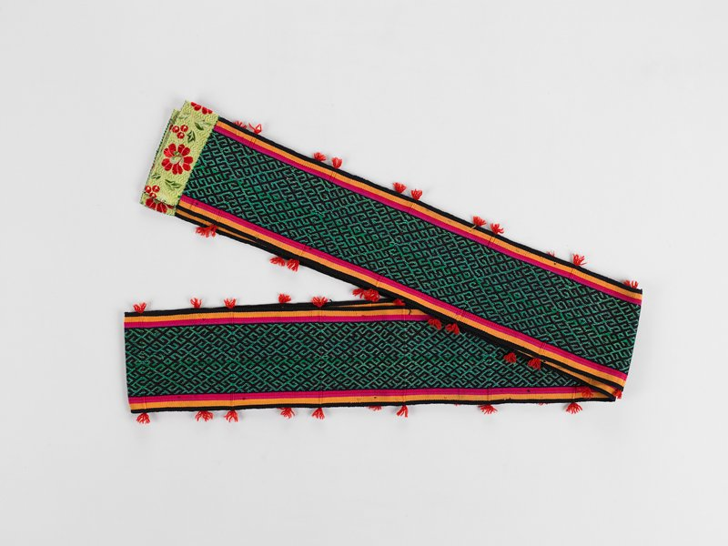 large central band of green and black diamond designs flanked on either side by three thin bands of fuscia, orange and black; ends finished in silk with floral pattern; small clumps of red fringe placed along both edges at equal intervals