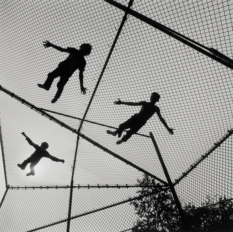 three boys lying on top of suspended fence