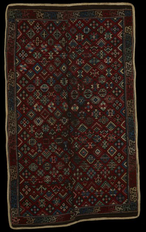 Yattha Dhenkhep; double panel wool brocade on wool background; discontinuous supplementary weft pattern in rose, pink, blues on dark brown ground; edges bound in cotton. Bed Covering
