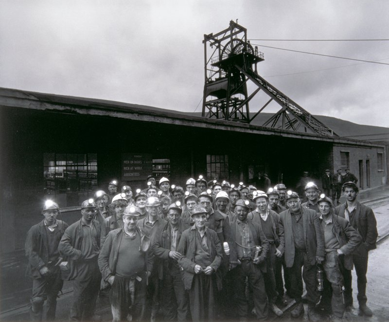 group of miners with hard hats in foreground; entrance to mine in background.