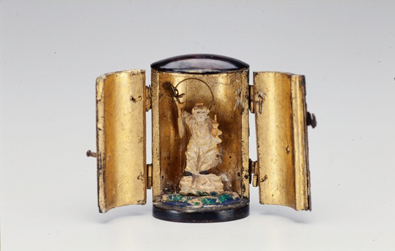 miniature case with double hinged doors on front opens to reveal a tiny figure standing on an animal and holding a small object in his proper left hand and a metal staff in his proper right hand; metal wire ring behind his head