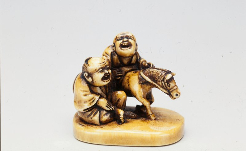two laughing men one seated on ground, other behind on a trotting horse; man on horse rests proper right hand on shoulder of seated man; bottom of netsuke is an oval form seal