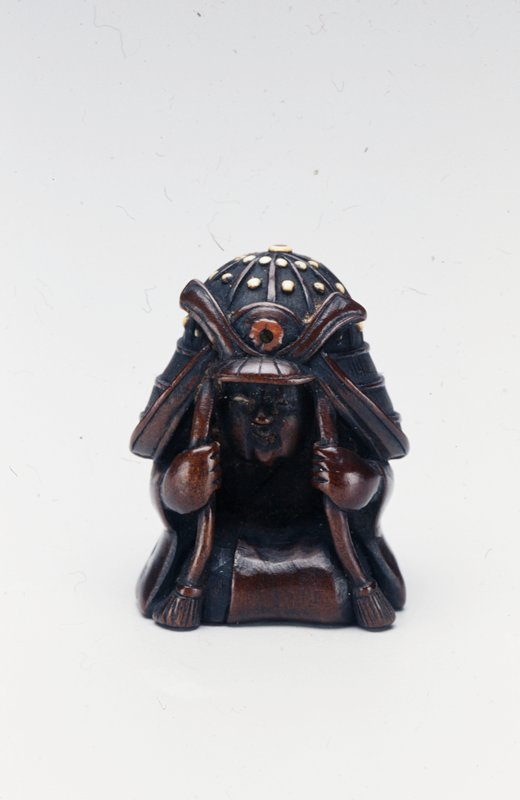 kneeling boy holding the straps of a large helmet he wears on his head; inlay on belt, helmet studs and in eyes