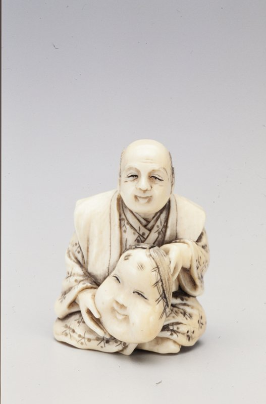 seated cross-legged, slightly smiling man holding an Okame mask