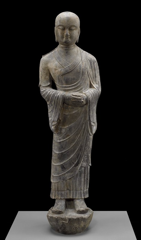 baldheaded figure with closed eyes, wearing a robe which falls in folds at stomach, lower arms and legs; slightly leaning to proper left, with a small space between proper right arm and body; hands folded at waist