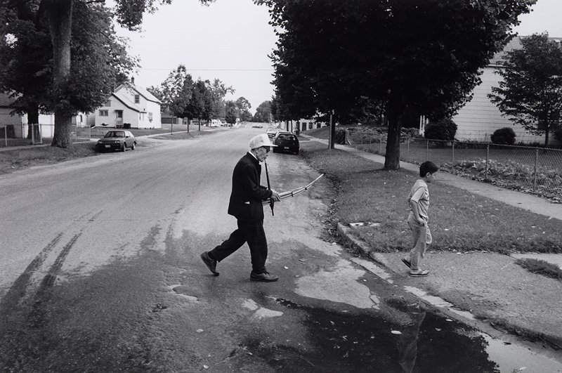 black and white photo of man walking, playing wind instrument with young boy in front