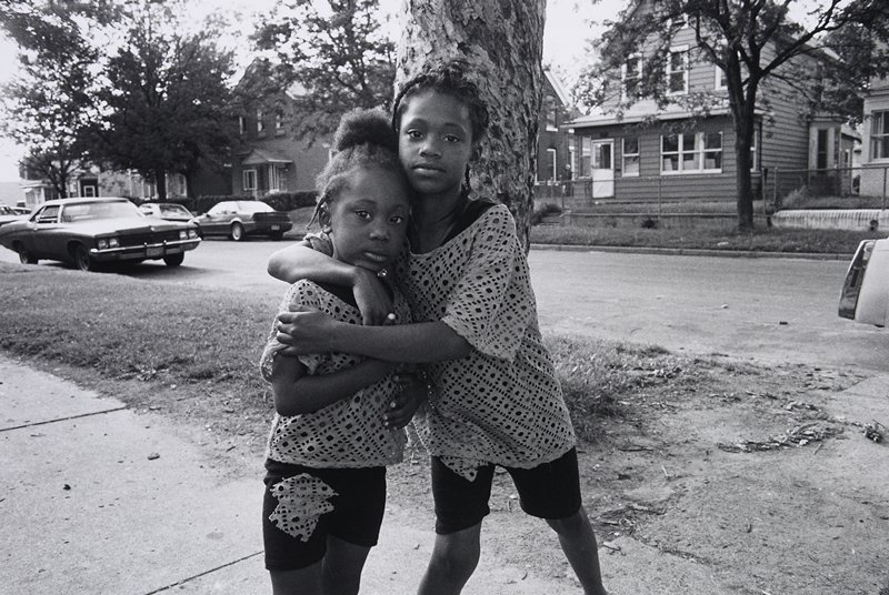 black and white photo of two young girls standing in front of tree