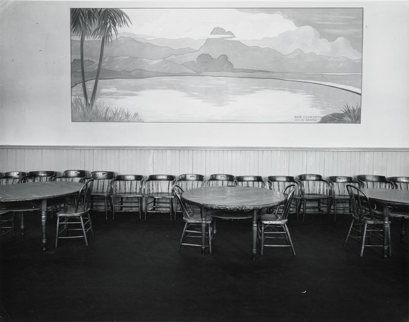 mural with water, mountains and tropical foliage; three tables with chairs around them in front; row of chairs against wall below mural