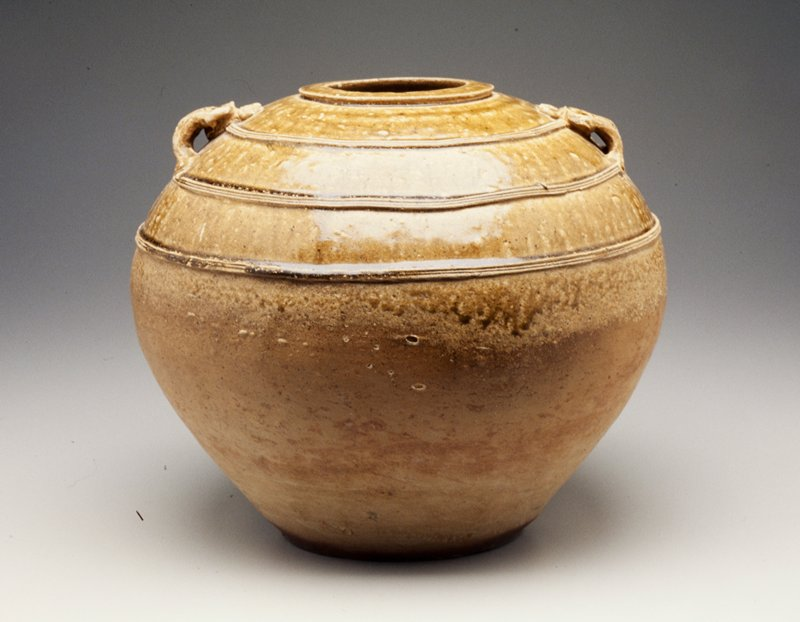 round-bodied jar with small foot; 2 applied handles with incised linear decoration; 3 rows of thin incised bands; top half glazed yellow-green