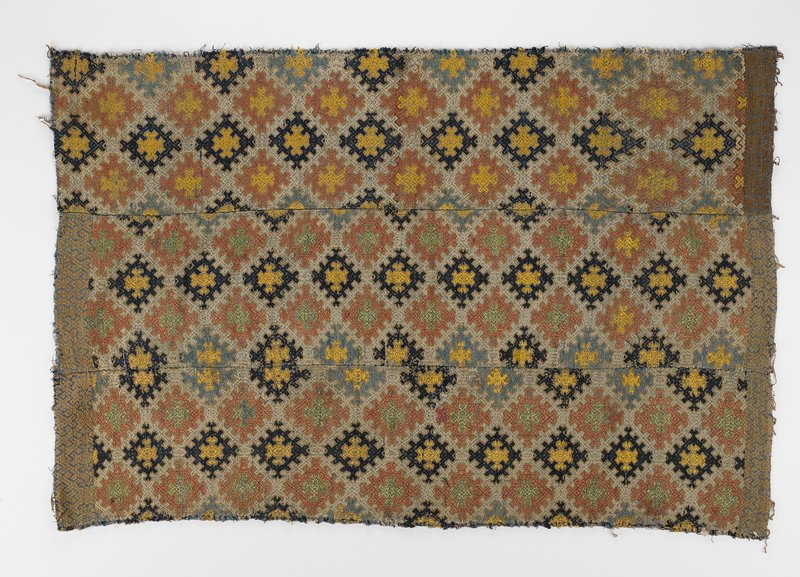 three woven panels sewn together; blue, yellow, green, white, and rust geometric design; border at both short ends of two panels; one panel has darker border on short end only