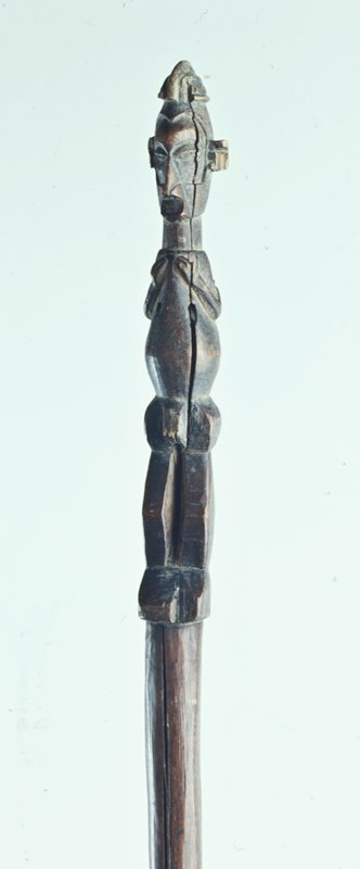 Straight staff with standing male figure on top, hands held to his chest