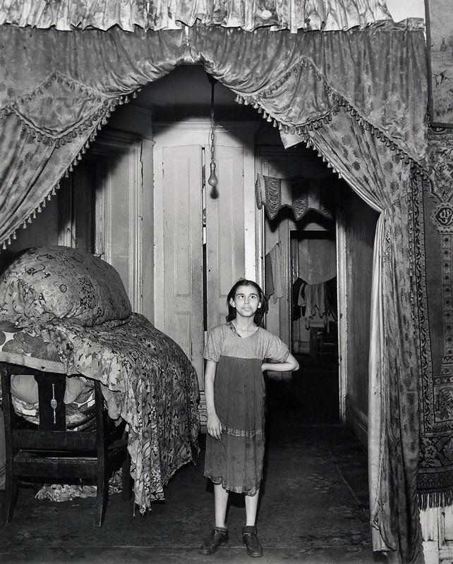 young woman with one cross eye wearing a soiled dress, standing in center of image with PL hand on hip; heavy tasseled drapes hanging over doorway; bundles of fabric on chairs at L; laundry visible hanging on clothesline in background at R; matted