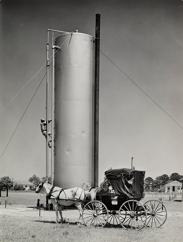 man climbing up the side of an oil heater-treater tower with a horse and buggy in front of it; houses in background; matted