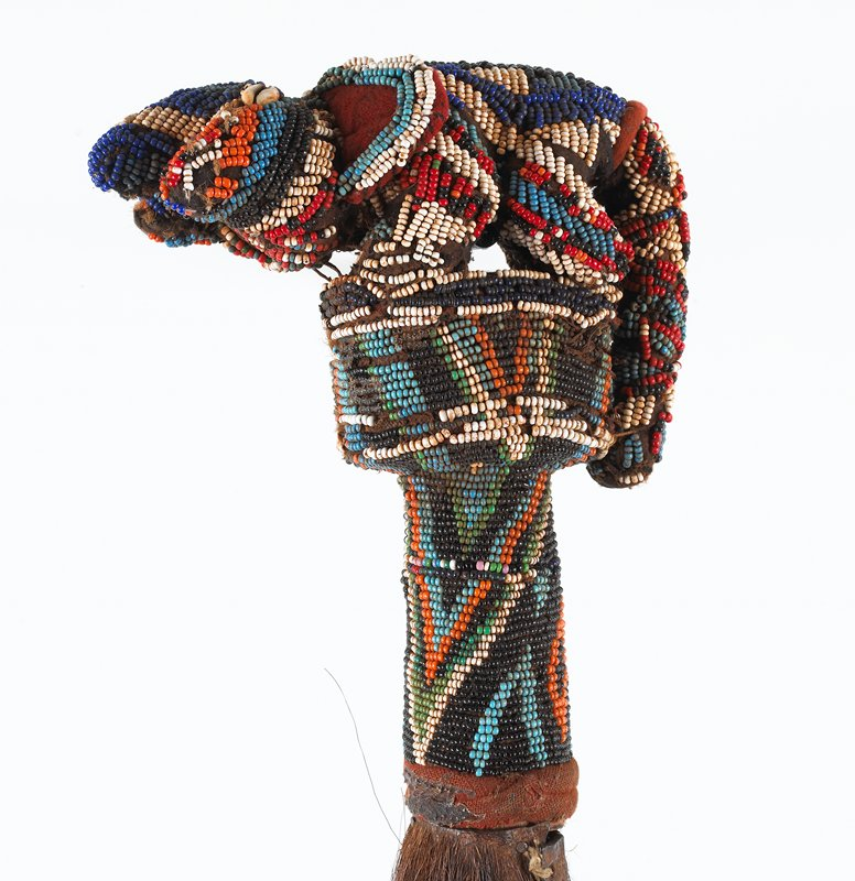 long horsehair tail with beaded finial in the shape of an elephant with a long tail and cowrie shell eyes