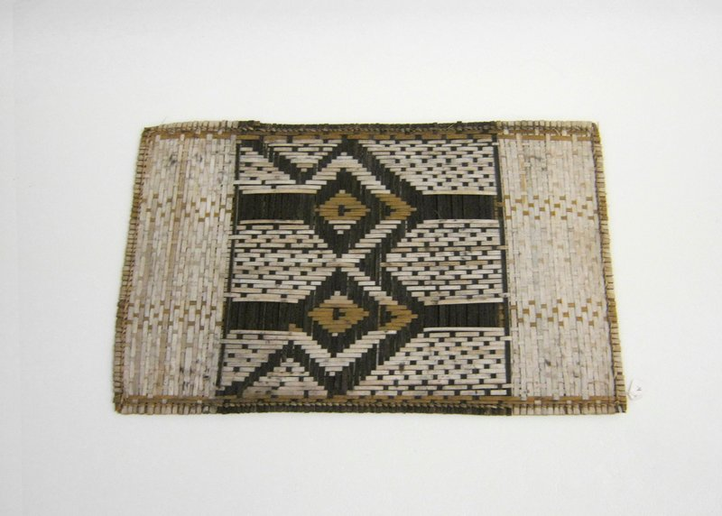 Small mat with geometric design at center in dark and light brown fibers flanked by bands of light tan