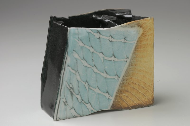 4-sided irregular box with divider at widest point; short sides and interior glazed black; long sides with blue and white linear pattern and tan area with incised lines